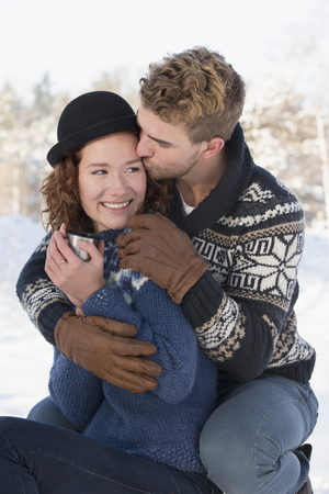 Caucasian couple kissing in snow