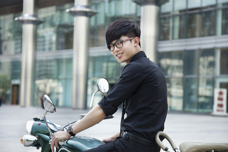 Chinese businessman sitting on motorcycle