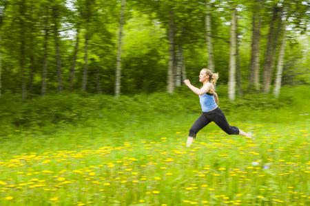 Blurred view of Caucasian woman running in tall grass Stok Fotoğraf