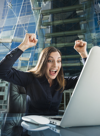 Caucasian businesswoman cheering at computer Foto de archivo