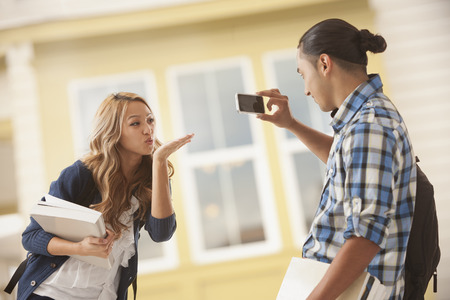 Man taking picture of girlfriend blowing kiss Stock Photo