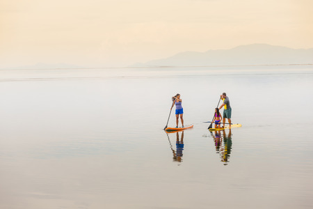 Family riding paddle boards