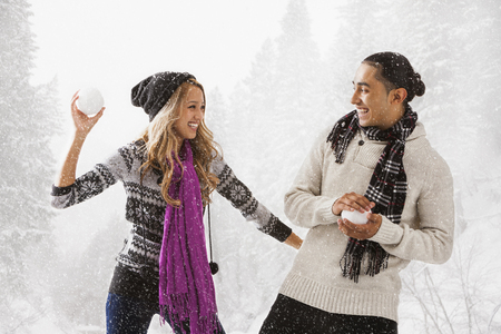 Couple having snowball fight outdoors Stock Photo