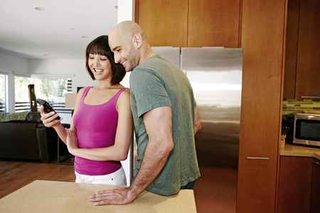 Couple using cell phone in kitchen