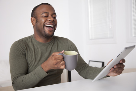 Black man drinking coffee and using digital tablet