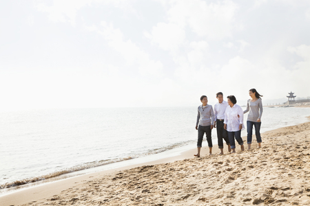 Chinese family walking on beach