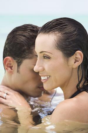 Hispanic couple hugging in water