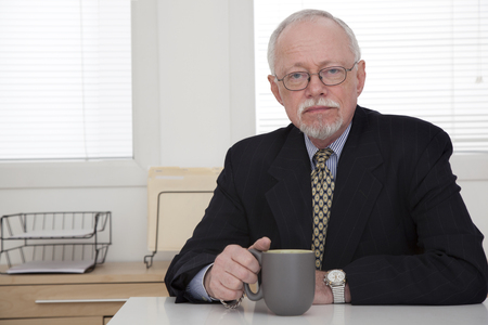 Caucasian businessman drinking coffee in office Stock Photo