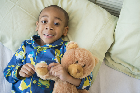 African American boy hugging teddy bear in bed