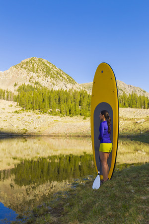 Hispanic woman with paddle board in rural landscape 免版税图像