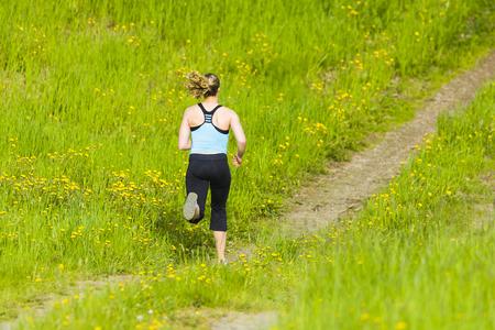 Caucasian woman running on path Stock Photo