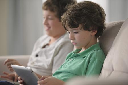 Garçon de race blanche à l'aide de tablette numérique sur canapé
