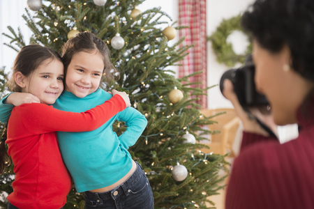 Mother taking picture of daughters by Christmas tree