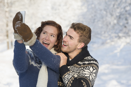 Caucasian couple taking pictures in snow Stock Photo