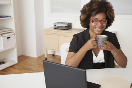 African American businesswoman drinking cup of coffee at desk Фото со стока