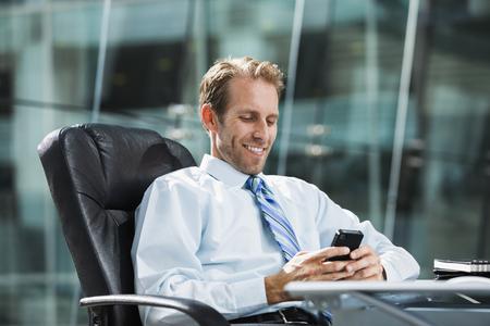 Caucasian businessman using cell phone at desk