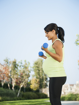 Pregnant Hispanic woman lifting weights outdoors Stock Photo