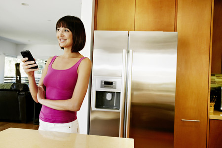 Mixed race woman using cell phone in kitchen