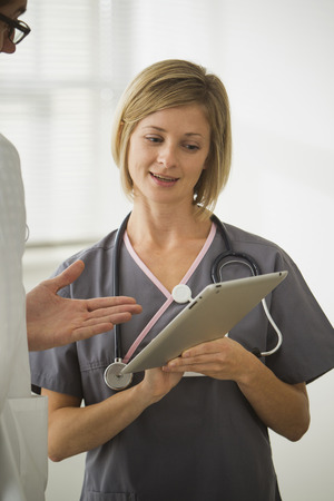 Caucasian nurse showing digital tablet to doctor