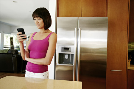 Mixed race woman using cell phone in kitchen Stock Photo - 107972910