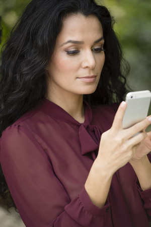 Hispanic woman using cell phone Stock Photo