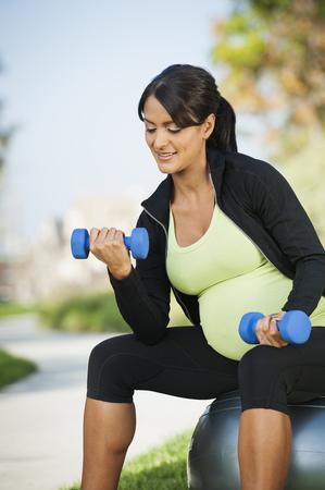 Pregnant Hispanic woman lifting weights outdoors