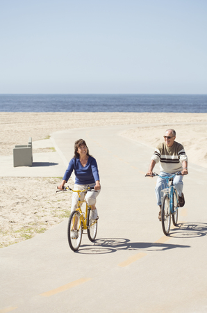 Couple riding bicycles on beach