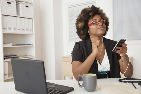 African American businesswoman listening to headphones at desk 스톡 콘텐츠 - 107910341