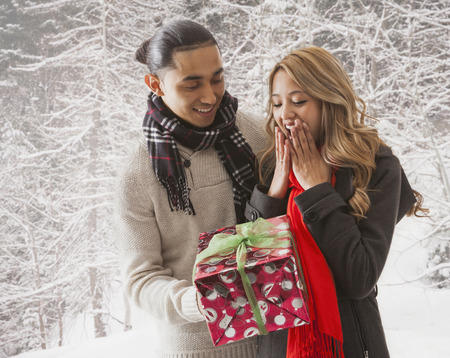 Man giving girlfriend gift in snow