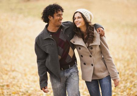 Couple marchant dans les feuilles d'automne
