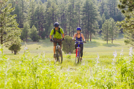 Couple riding mountain bikes in meadow