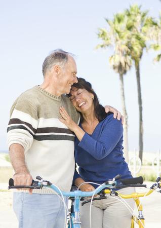 Couple walking bicycles on beach Stock Photo