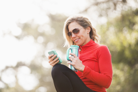Caucasian woman using cell phone outdoors Stock Photo