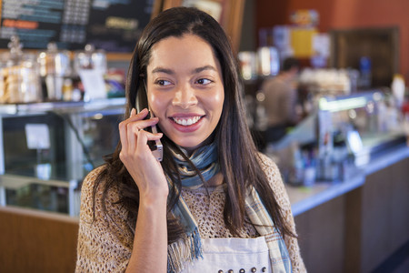 Mixed race woman on telephone in coffee shop