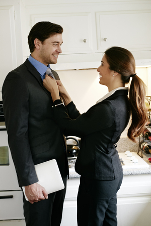 Woman tying husbands tie in kitchen Stock Photo