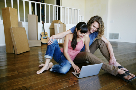Couple using laptop in new home