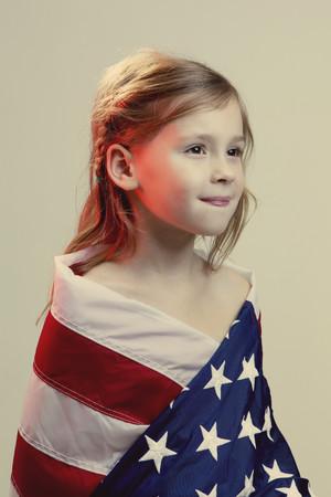 Fille caucasienne enveloppée dans le drapeau américain Banque d'images
