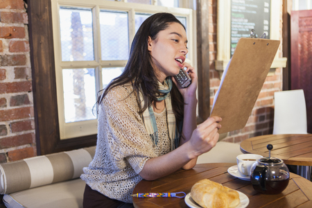 Mixed race woman reading menu in cafe