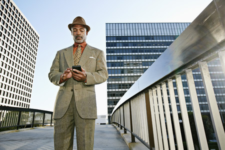 Black businessman using cell phone on urban walkway