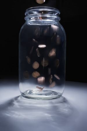 Coins falling into empty change jar Imagens