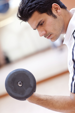 Hispanic man lifting weights in gym Stock Photo