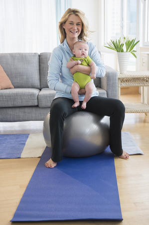 Caucasian mother holding baby on exercise ball
