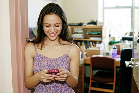 Mixed race college student using cell phone in dorm Stok Fotoğraf