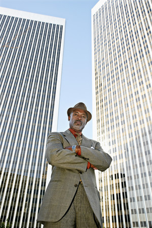 Black businessman standing in front of highrises 免版税图像 - 107923217