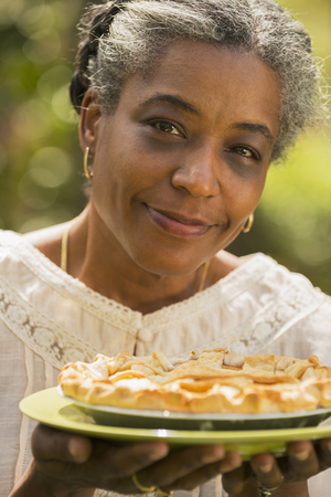 Mixed race woman holding fruit pie outdoors