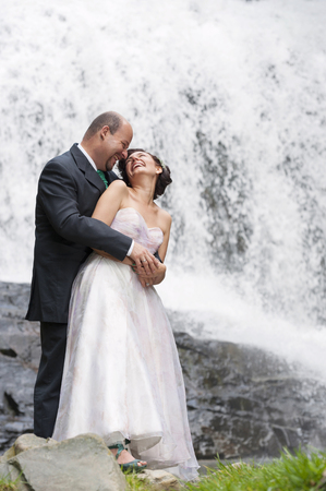 Hispanic newlyweds hugging by waterfall