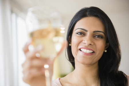 Indian woman toasting with glass of wine