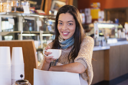Mixed race woman sitting in coffee shop Stock Photo