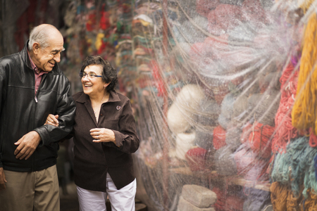 Older Hispanic couple admiring yarn for sale Stock Photo