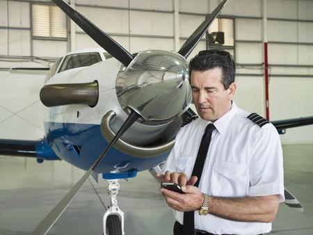 Caucasian pilot using cell phone in hangar Reklamní fotografie